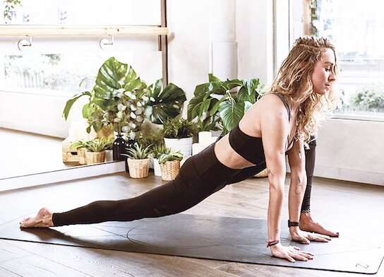 Female yoga instructor doing lunge on yoga mat in yoga studio.