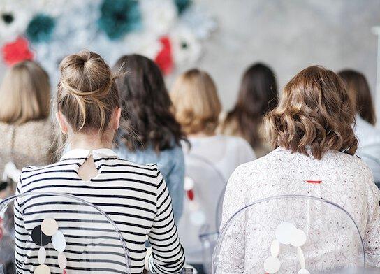 Female audience watching training presentation.