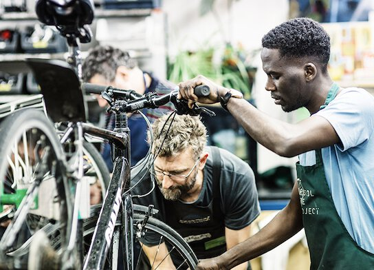 Bike mechanic and student working on bicycle at bike maintenance class.