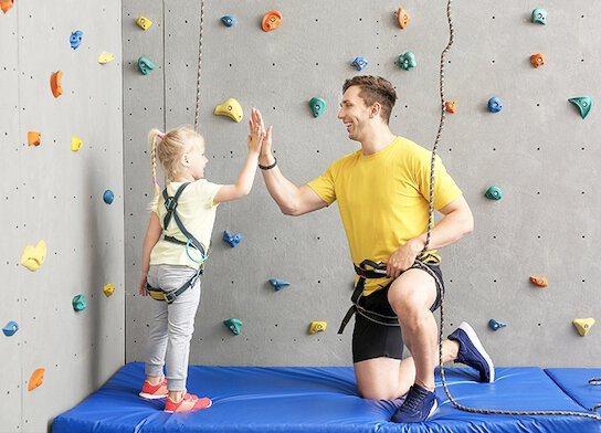 Climbing instructor with girl student at climbing centre.