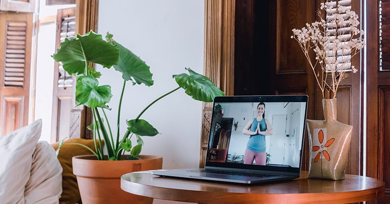 Laptop on a table showing an online yoga class