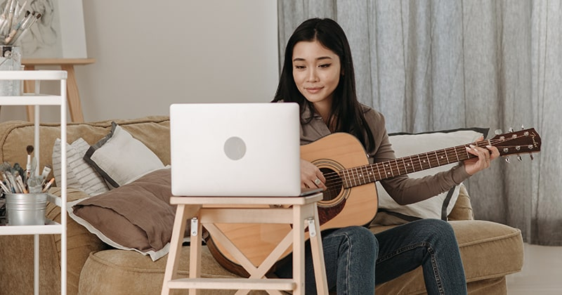 Lady learning to play the guitar from a laptop
