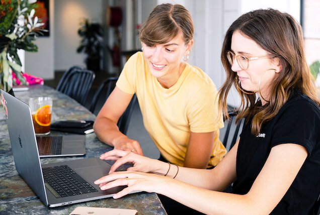 Two female franchise owners using franchise booking system on laptop.